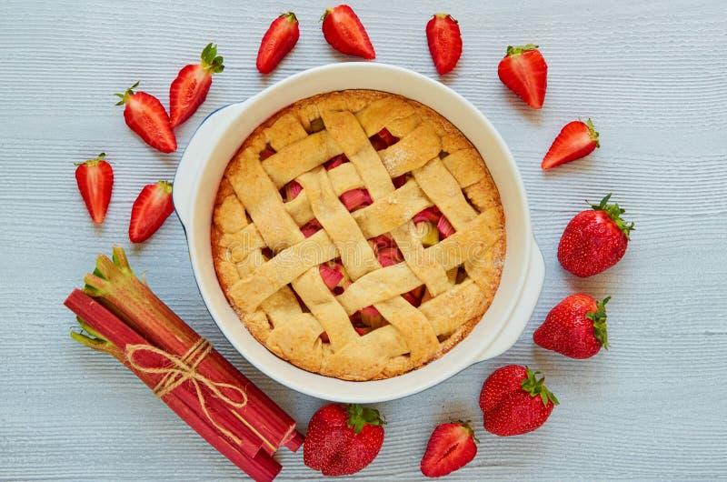 Tarte de fraise de rhubarbe dans le plat de cuisson sur la table de cuisine grise Tarte végétarienne décorée des fraises coupées  photographie stock libre de droits