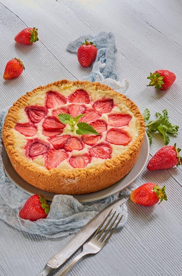 Tarte de fraise sur le fond gris de cuisine Gâteau au fromage de baies décoré des fraises fraîches organiques et des feuilles en  photos libres de droits