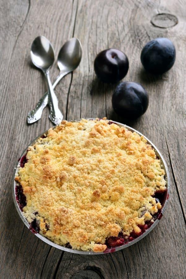 Tarte de miette de prune dans la casserole sur le fond en bois photo stock
