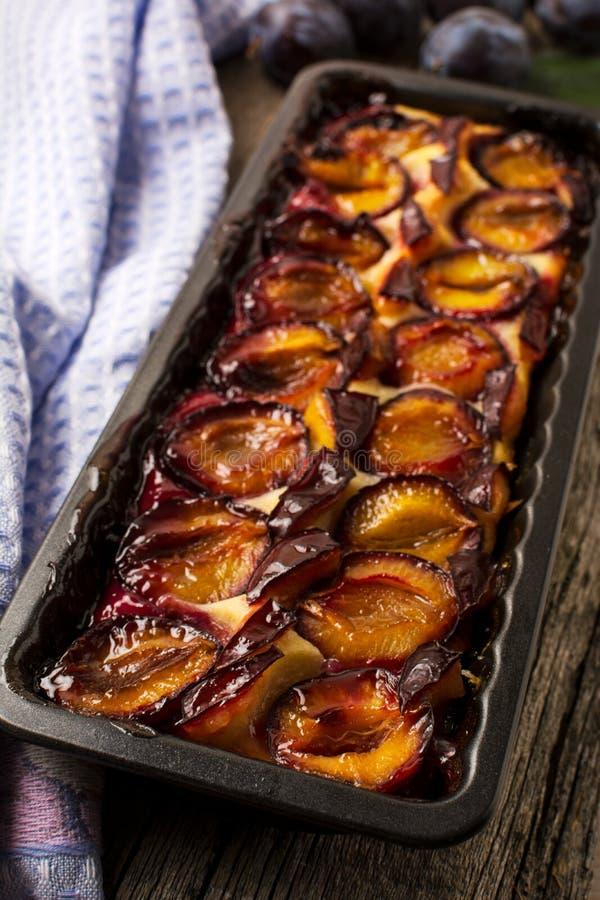 Tarte de prune dans le plateau de cuisson sur la table en bois image libre de droits