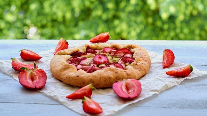 Tarte faite maison de fraise sur la table de cuisine grise décorée des fraises coupées en tranches fraîches Galette sain végétari image stock