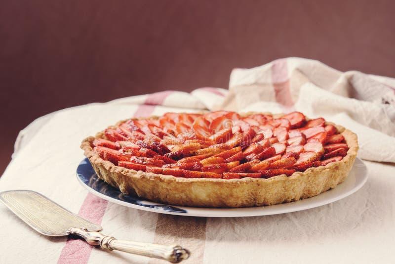 Tarte faite maison fraîche de fraise avec la crème anglaise sur la nappe rustique photo stock