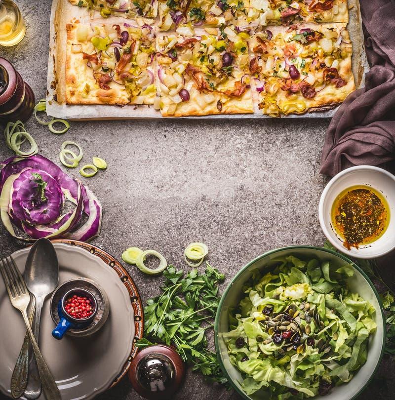 Tarte flambee lub otwarty jarzynowy kulebiak z warzywami i zieloną sałatką na nieociosanym kuchennego stołu tle z talerzami, cutl obraz stock