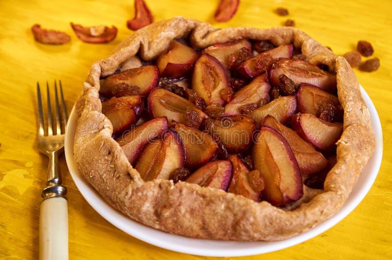 Tarte gratuit de sucre avec des prunes et des raisins secs d'un plat blanc sur le fond en bois jaune décoré des prunes fraîches,  image libre de droits