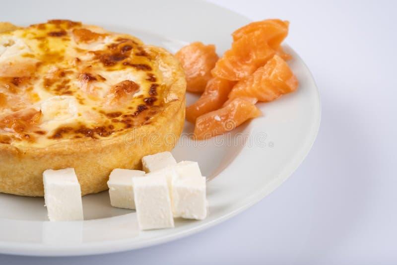 Tarte ou cocotte en terre avec les saumons et le feta du plat blanc photos stock