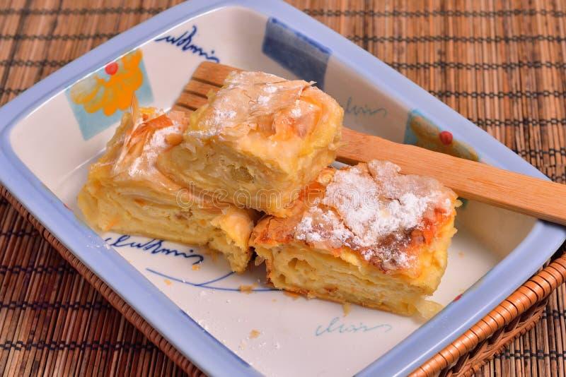 Tarte roumain de fromage avec la cuillère en bois dans un plat photos stock