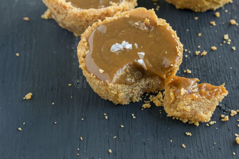 Tarte salée de caramel avec la croûte de beurre de miette sur la table noire rustique photo libre de droits