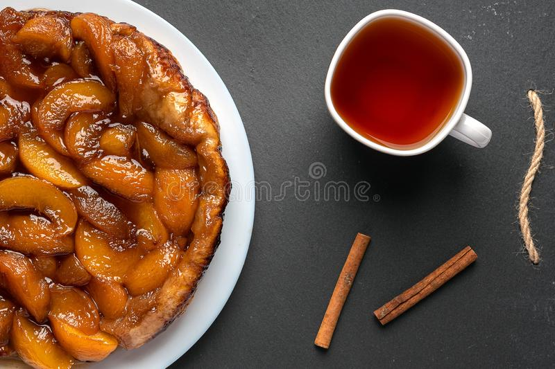Tarte Tatin with peaches and caramel on a white plate on a dark background. Next to the white cup with black tea and cinnamon royalty free stock image
