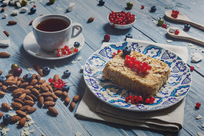 Tarte, thé, café et baies de pâtisserie au bois rustique bleu images stock
