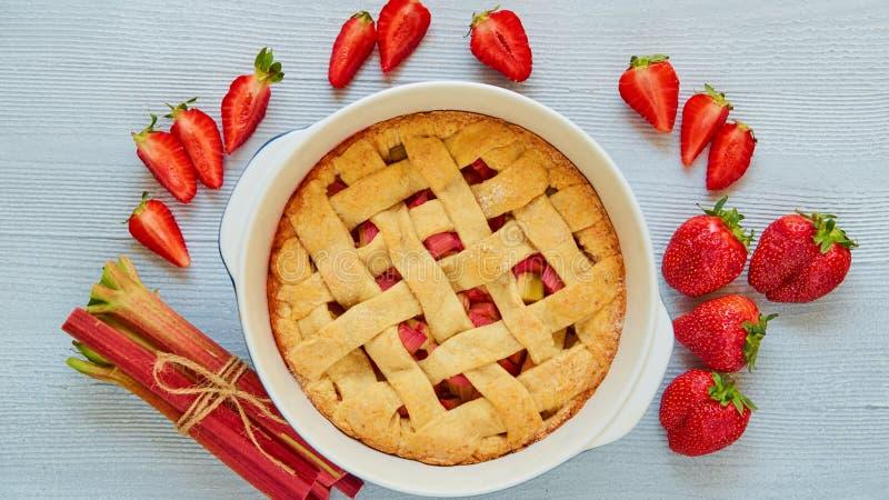 Tarte traditionnel de fraise de rhubarbe dans le plat de cuisson sur la table de cuisine grise Tarte végétarienne décorée des fra image stock
