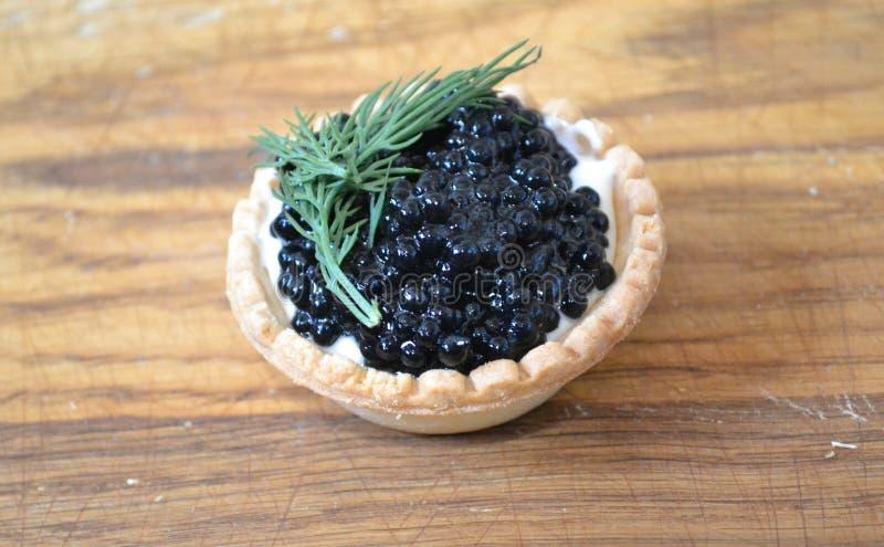 Tartelette avec du beurre et le caviar noir photographie stock