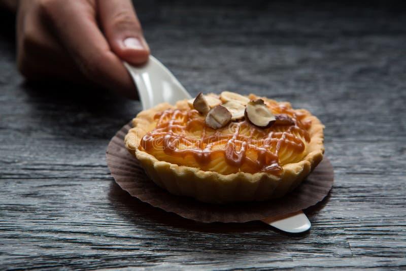 Tartelette avec le caramel et les écrous Tarte appétissante délicieuse sur un fond en bois foncé images libres de droits