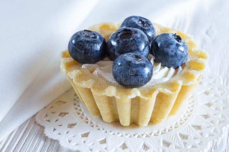 Tartelette ou gâteau avec le fromage de myrtille et fondu frais sur le fond en bois blanc images stock