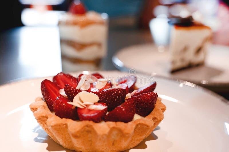 Tartelette saporito del dolce in piatto bianco con le fragole sulla cima immagini stock