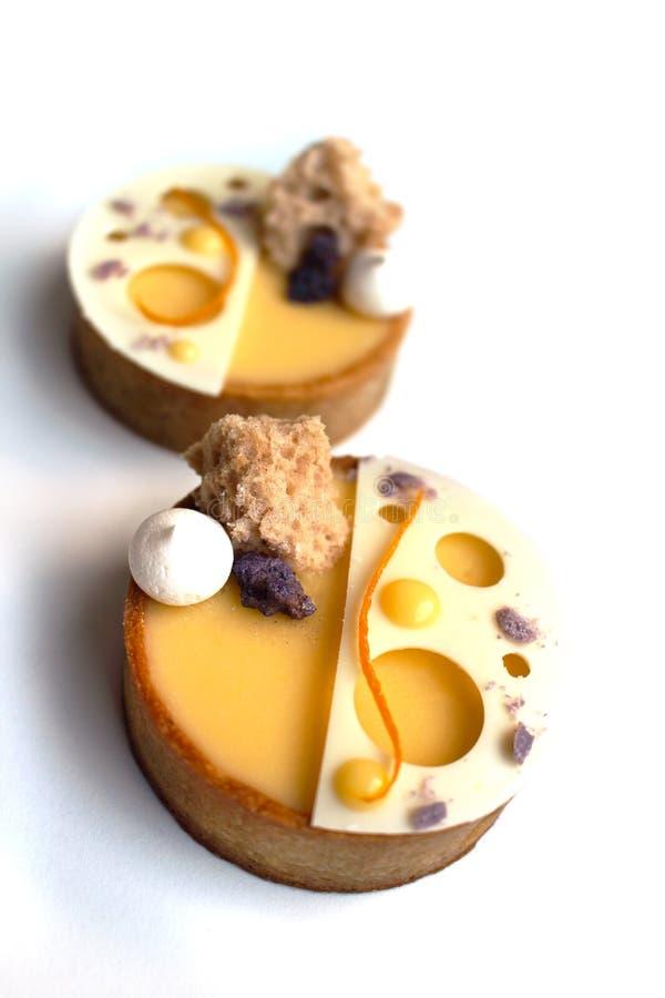 Tartelettes arancio con meringa, la spugna di microonda e la decorazione della cioccolata bianca su fondo bianco immagine stock