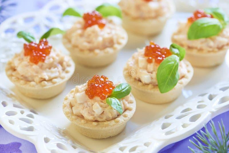Tartelettes avec de la salade de fruits de mer, le caviar rouge et le basilic photographie stock