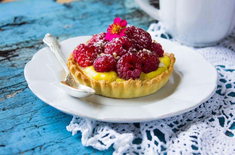 Tartelettes délicieuses de framboise avec de la crème de vanille sur le fond en bois bleu Vue supérieure image libre de droits