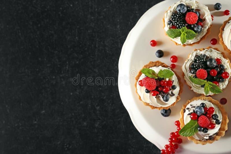 Tartelettes savoureuses avec de la crème et les baies fouettées sur le support de dessert, vue supérieure photographie stock libre de droits