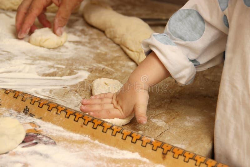 Tartes de cuisson de femme dans la cuisine avec la petite petite-fille d'une-deux La grand-maman fait cuire des tartes et apprend photos stock