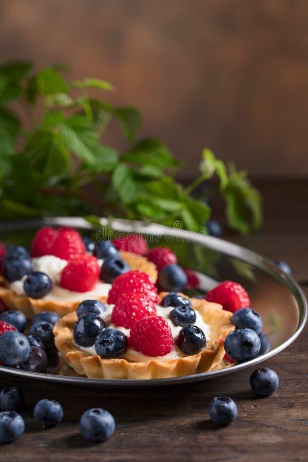 Tartes de dessert avec des framboises et des myrtilles sur un tabl en bois image stock
