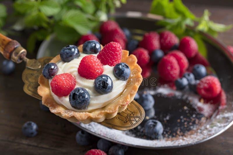 Tartes de dessert avec des framboises et des myrtilles sur un tabl en bois image libre de droits