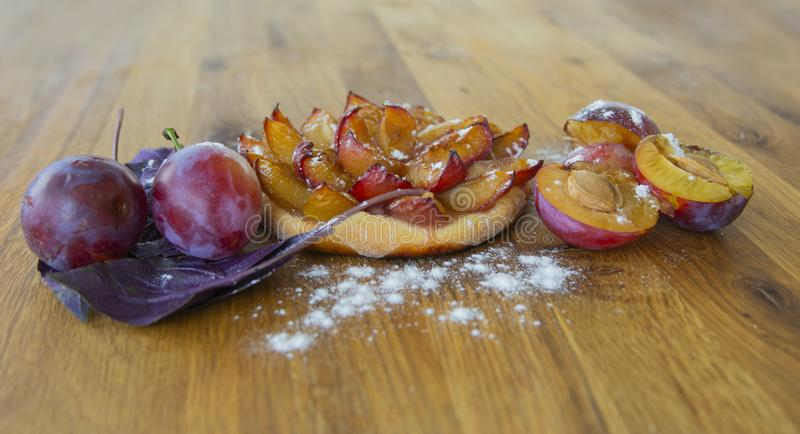 Tartlet da ameixa fresca, fruto fresco da ameixa em uma placa de madeira foto de stock