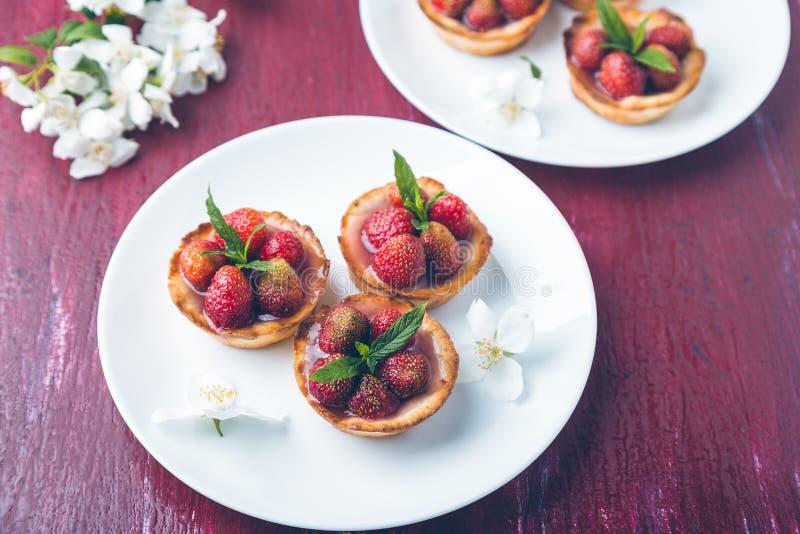 Tartlet de la fresa en las placas blancas en fondo rojo Foto entonada Flor adornada foto de archivo libre de regalías