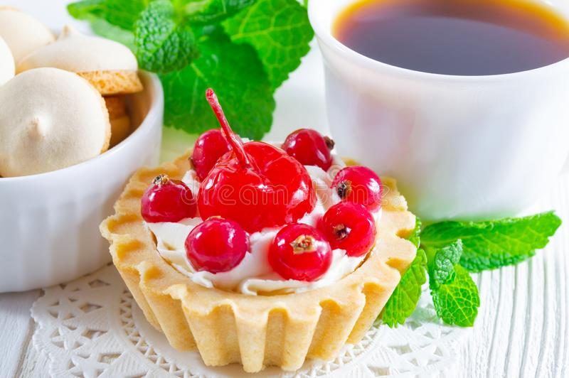 Tartlet delicioso con las bayas y queso cremoso fresco, una taza de té y pequeñas galletas fotografía de archivo