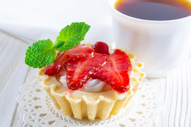 Tartlet mit frischem Erdbeere- und Frischkäse und eine Tasse Tee und kleine Plätzchen stockfotografie