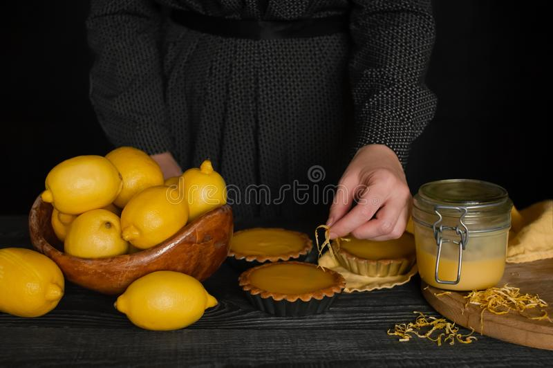 Tartlets μαγείρων γυναικών με τη στάρπη λεμονιών στοκ φωτογραφίες
