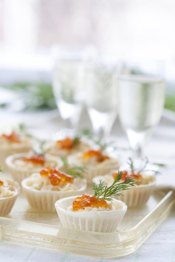 Tartlets με το τυρί κρέμας και κόκκινο στενό επάνω χαβιαριών Πρόχειρα φαγητά με το κόκκινο χαβιάρι με το απεριτίφ Ελαφριά ανασκόπ στοκ φωτογραφίες με δικαίωμα ελεύθερης χρήσης