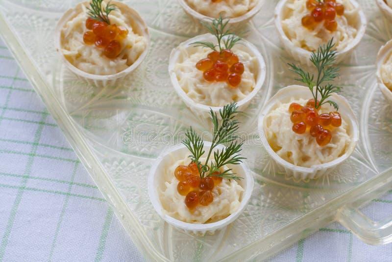 Tartlets με το τυρί κρέμας και κόκκινο στενό επάνω χαβιαριών Πρόχειρα φαγητά με το κόκκινο χαβιάρι με το απεριτίφ Ελαφριά ανασκόπ στοκ εικόνες
