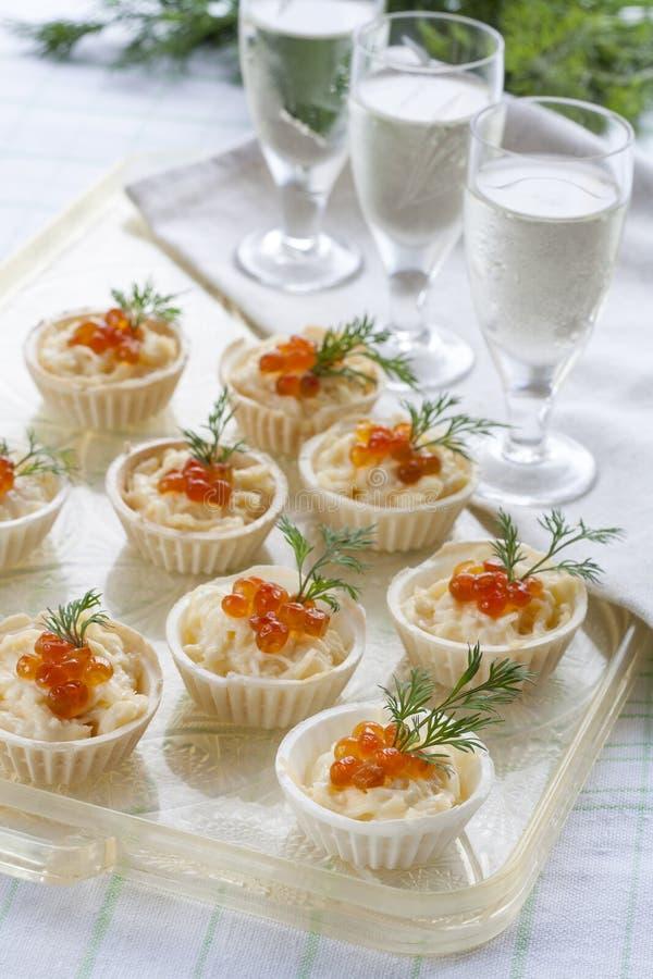Tartlets με το τυρί κρέμας και κόκκινο στενό επάνω χαβιαριών Πρόχειρα φαγητά με το κόκκινο χαβιάρι με το απεριτίφ Ελαφριά ανασκόπ στοκ φωτογραφία με δικαίωμα ελεύθερης χρήσης