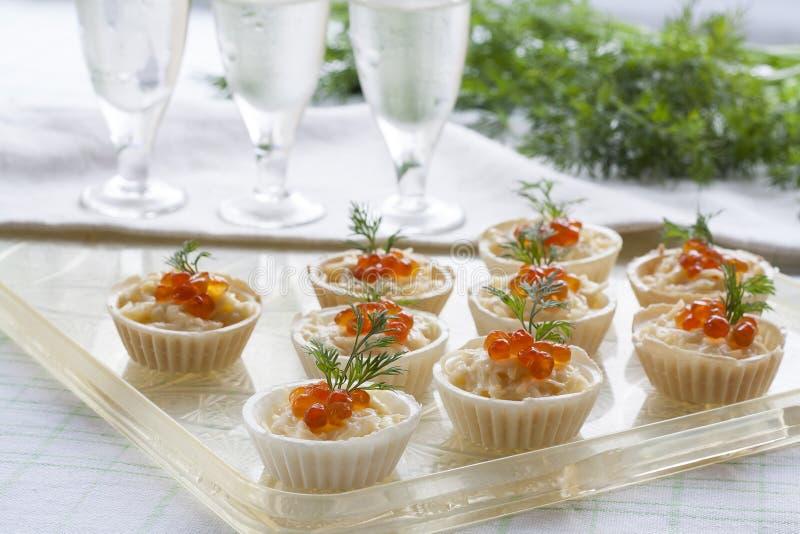 Tartlets με το τυρί κρέμας και κόκκινο στενό επάνω χαβιαριών Πρόχειρα φαγητά με το κόκκινο χαβιάρι με το απεριτίφ Ελαφριά ανασκόπ στοκ εικόνα