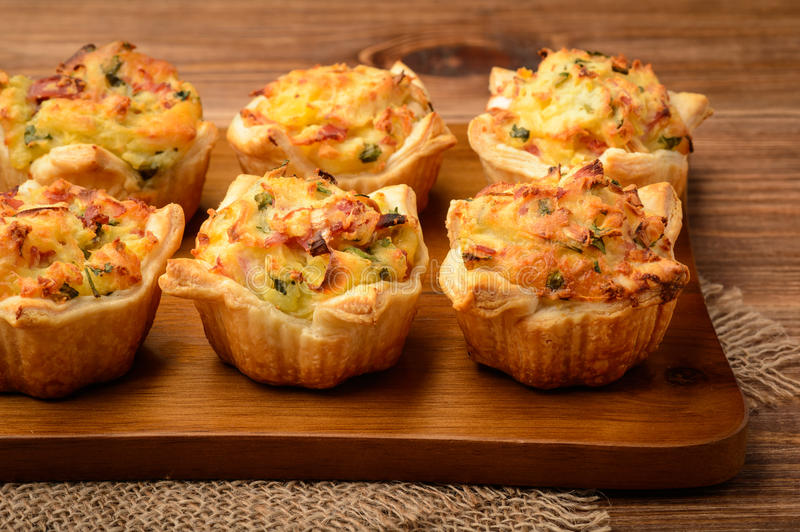 Tartlets baked with mashed potato, cheese, ham and parsley, on wooden background. royalty free stock photography