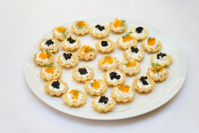 Tartlets with black and red caviar on a white plate royalty free stock photography