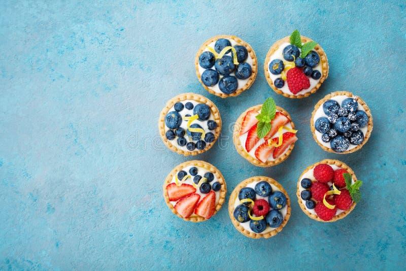 Tartlets of cake met hierboven roomkaas en bes op turkooise lijst van Heerlijk kleurrijk gebakjedessert royalty-vrije stock foto