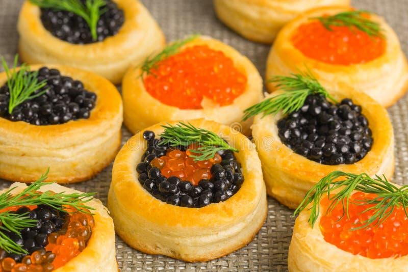 Tartlets con cierre rojo y negro del caviar para arriba fotos de archivo libres de regalías