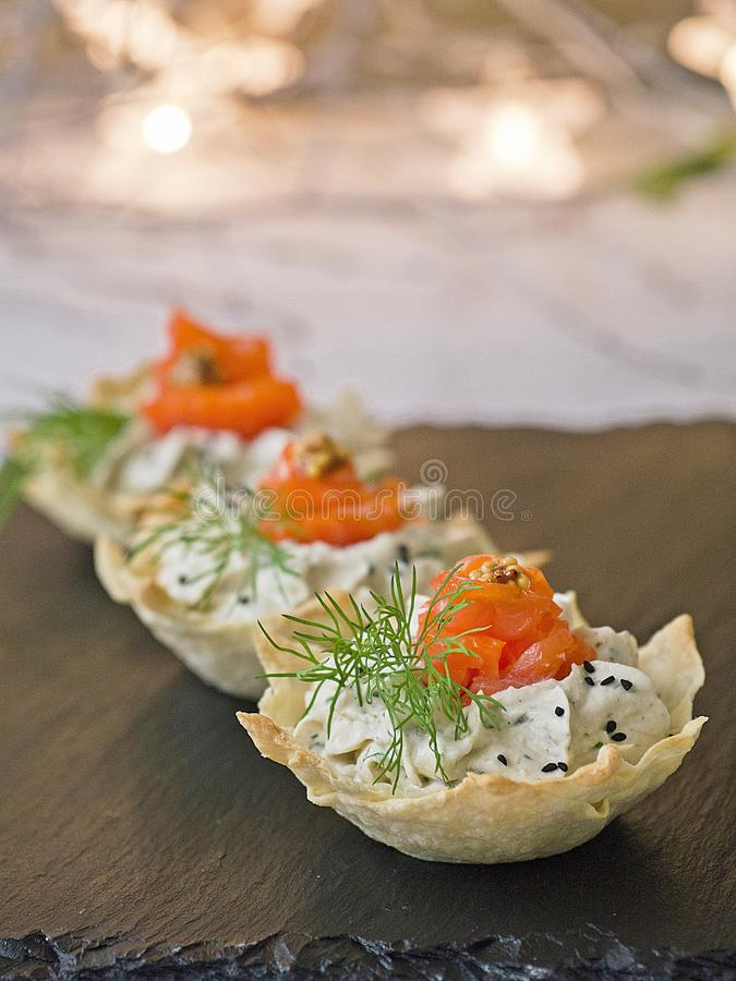 Tartlets with cream cheese and smoked salmon on black slate. Festive New Year`s dish. Christmas snack. Close up, copy space, stock image