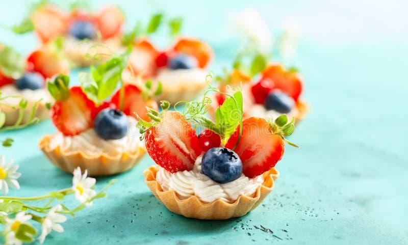 Tartlets de la baya del verano con las bayas poner crema y frescas imagenes de archivo