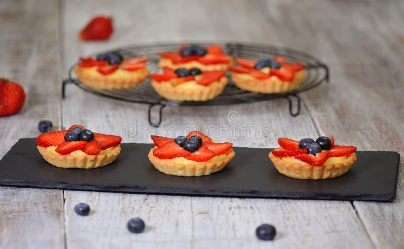 Tartlets de la baya del verano con las bayas poner crema y frescas Postre sano de los pasteles del verano para el partido foto de archivo