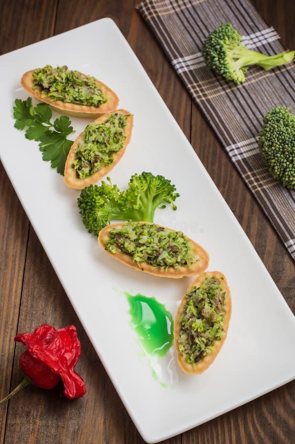 Tartlets faszerowali z minced mięsnym tuńczykiem i brokułami Drewniany tło zdjęcie royalty free