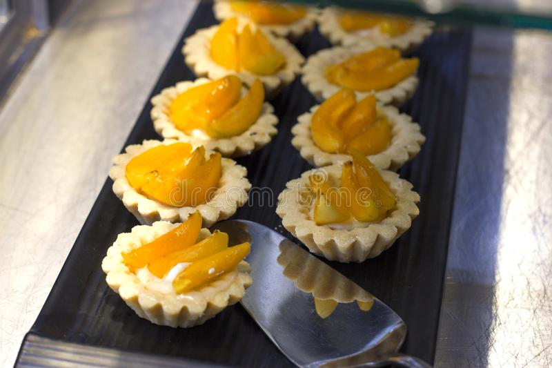 Tartlets with fresh peaches and arbicos on a black tray royalty free stock photos