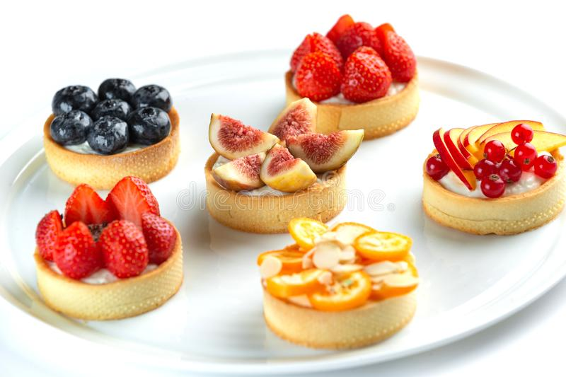Tartlets with fruits and berries on an isolated white background. Tartlets with fruits and berries in a plate close-up on an isolated white background stock image
