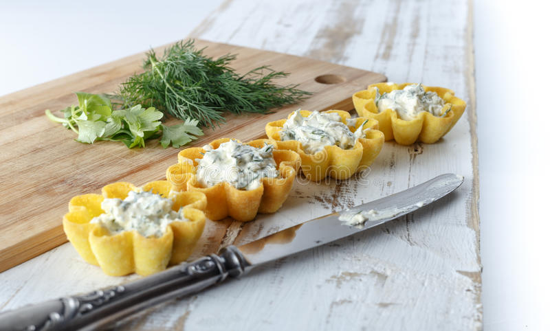 Tartlets fyllde med ost- och dillsallad mot lantlig träbakgrund arkivfoton