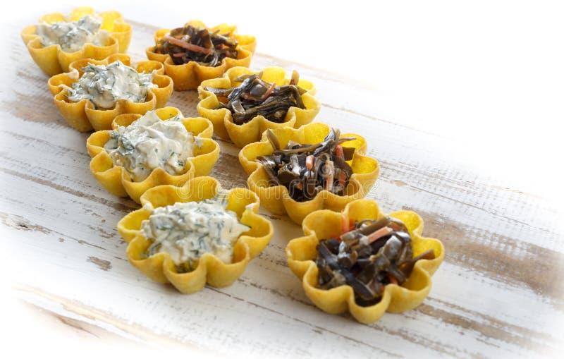 Tartlets fyllde med ost- och dillsallad och havsväxtsallad mot lantlig träbakgrund royaltyfri bild