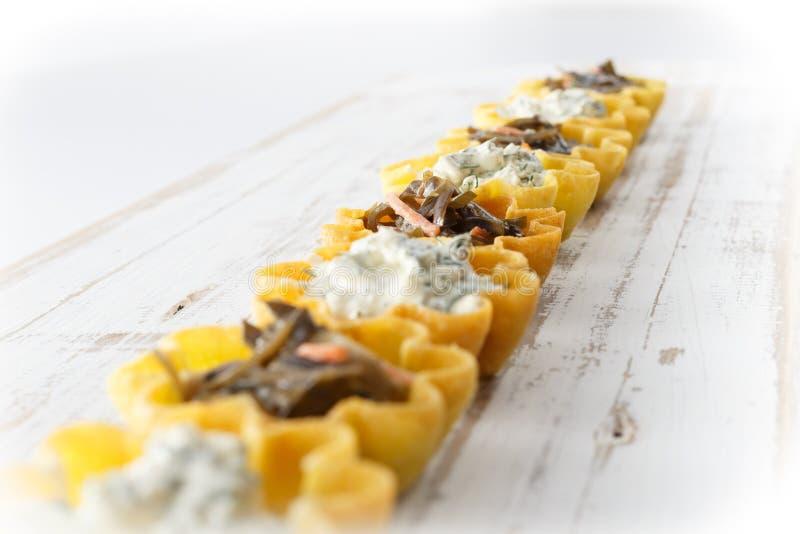 Tartlets fyllde med ost- och dillsallad och havsväxtsallad mot lantlig träbakgrund arkivbilder