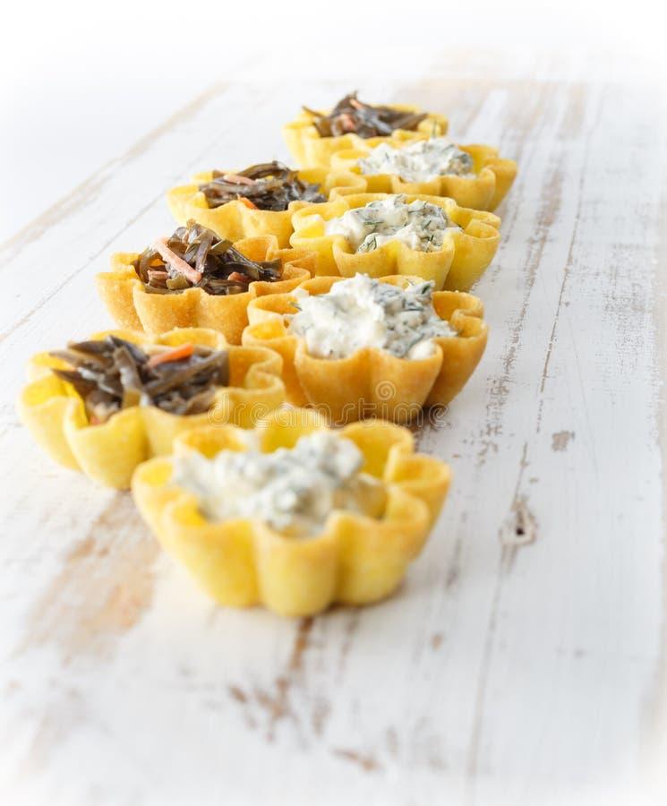 Tartlets fyllde med ost- och dillsallad och havsväxtsallad mot lantlig träbakgrund royaltyfria foton