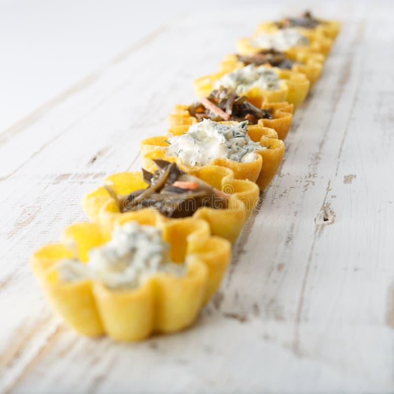 Tartlets fyllde med ost- och dillsallad och havsväxtsallad mot lantlig träbakgrund royaltyfri fotografi