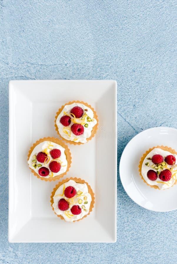 Tartlets hechos en casa de la frambuesa adornados con las nueces de pistacho y el ?nimo de lim?n imagen de archivo